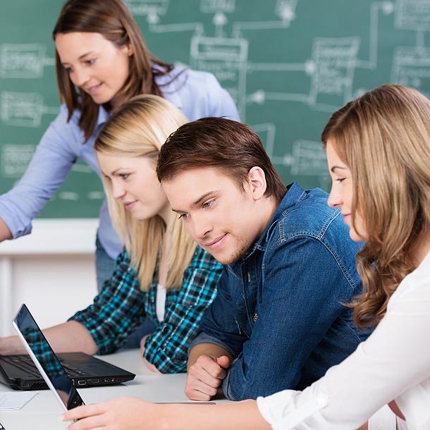 : Junge Leute sitzen mit Notebooks an einem Tisch. Im Hintergrund sieht man eine grüne, mit Kreide beschriebene Tafel.