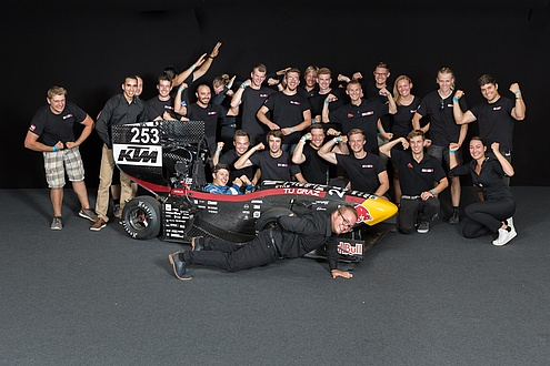 Gruppe Studierender posieren hinter eine Rennboliden