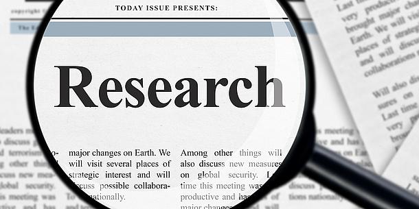 """Eine Lupe vergrößert auf einer Zeitung das Wort """"Research""""."""