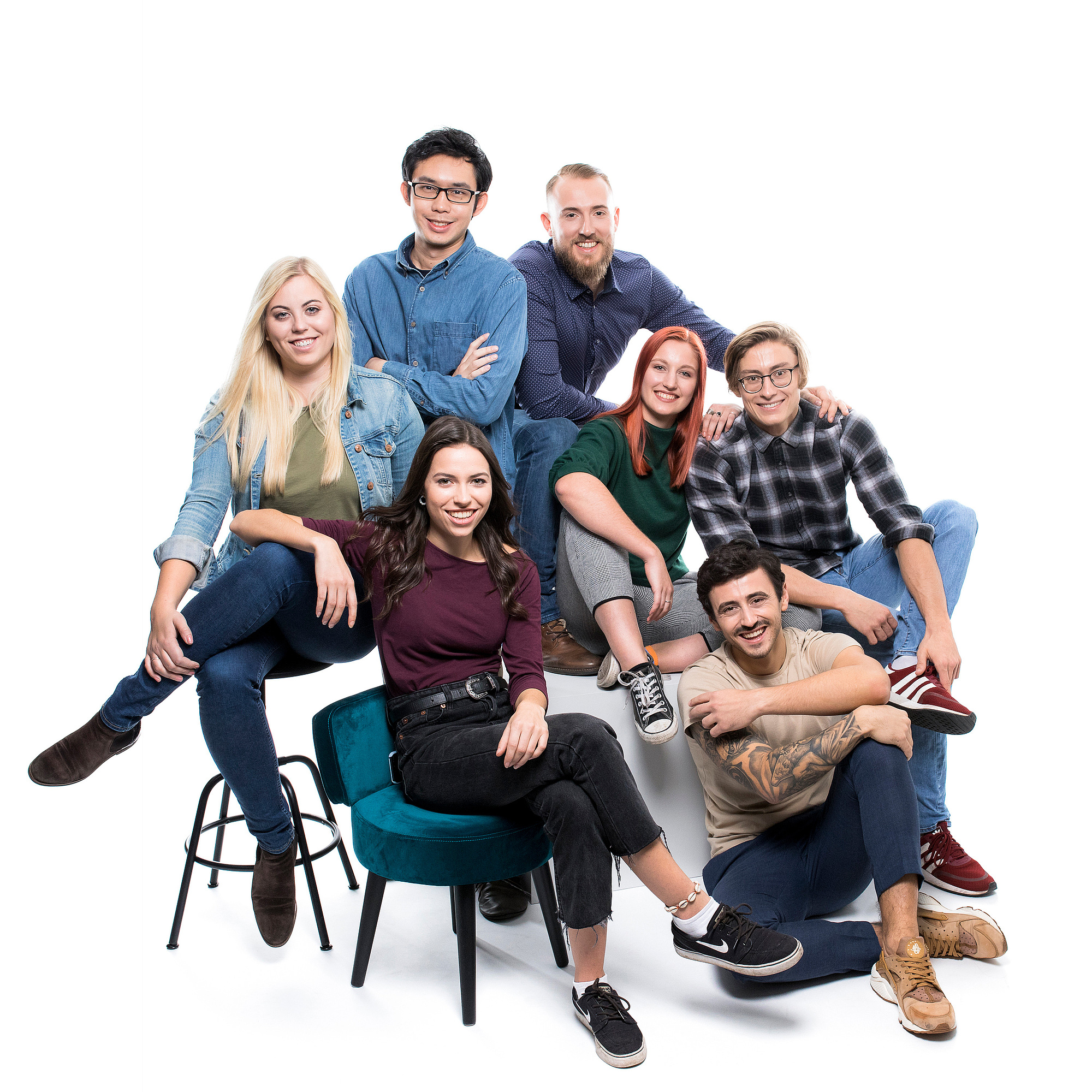 7 junge Leute sitzen auf Blöcken und halten Gegenstände wie ein Notebook, ein Reagenzglas, ein Betonmodell oder eine Platine in der Hand.