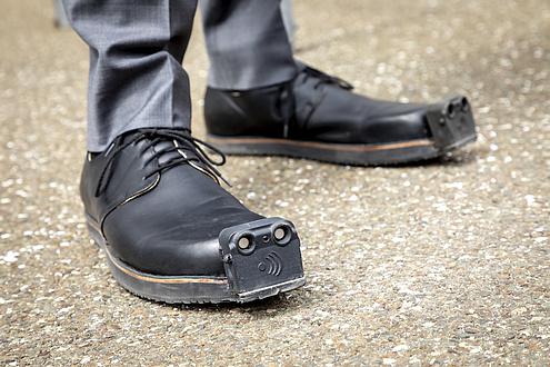Füße mit Schuhen, an der Schuhspitze ist ein Ultraschallsensor montiert