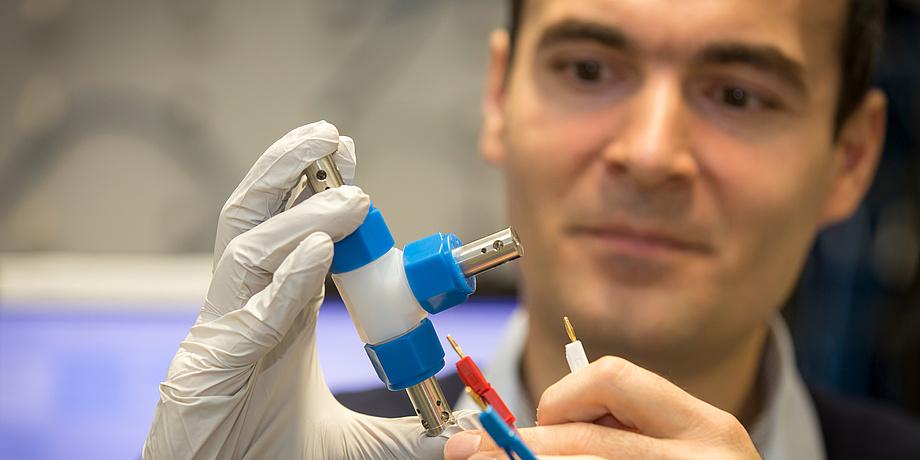 Ilie Hanzu mit einer Batterie und Kabel in den Händen.