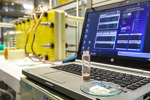 Detailaufnahme Glasgefäß vor Bildschirm und Apparatur