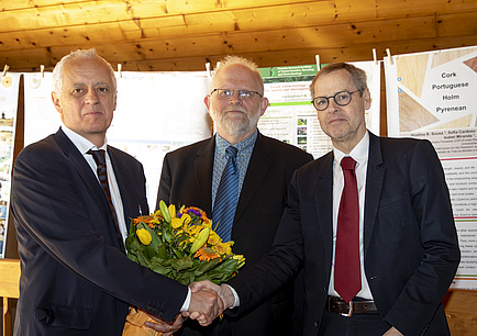 Three men in suits shake hands, the left one gets a bouquet of flowers.