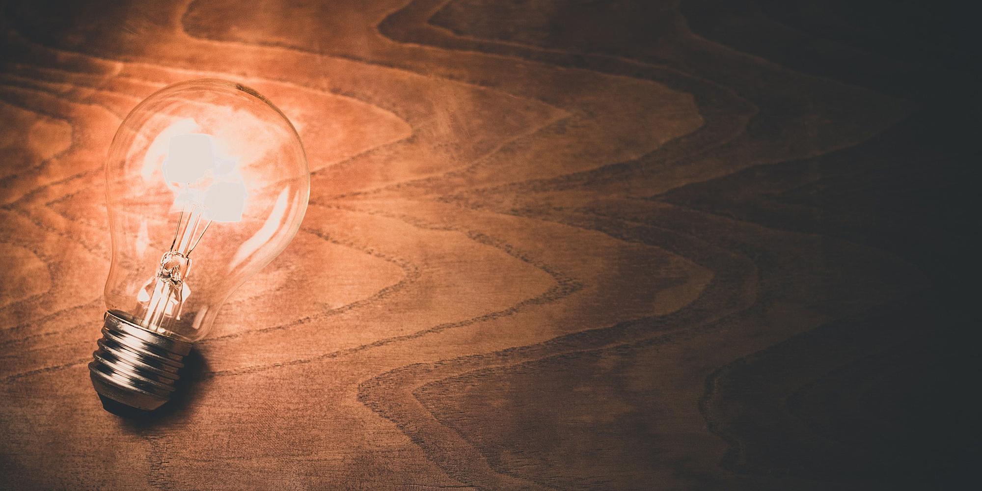 leuchtende Glühbirne auf Holzoberfläche