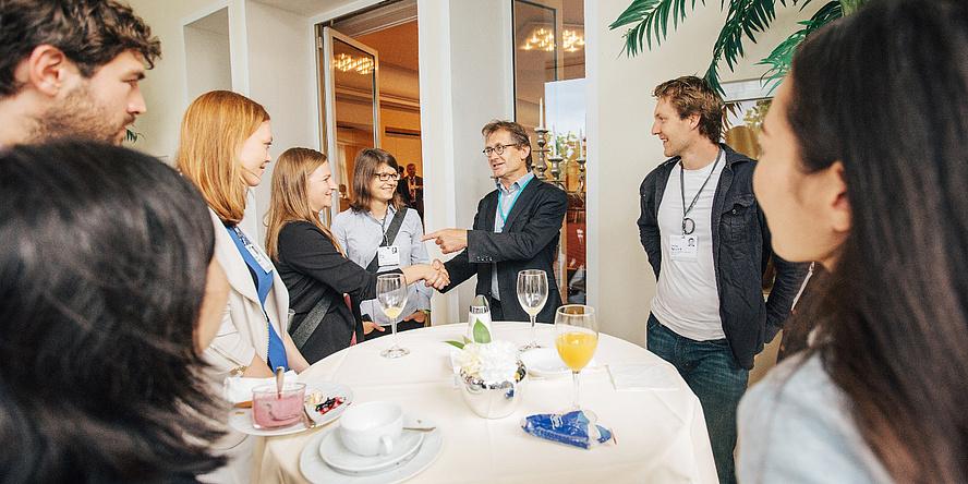 Am Stehtisch beim Science Breakfast begrüßen die jungen TU Graz-Wissenschaftlerinnen Anna Eibel und Beate Steller Bernard Feringa, umringt von anderen Teilnehmerinnen und Teilnehmern des Meetings.