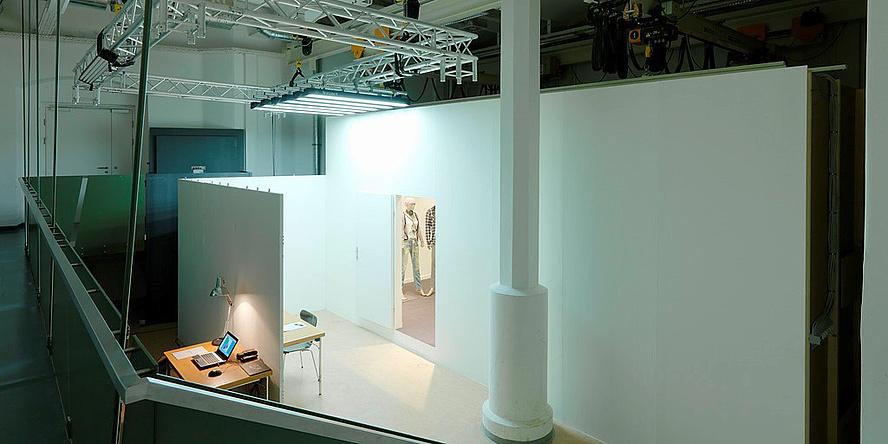 Ein hallenartiger Raum, in dem weiße Wände und Säulen zu sehen sind. Alles ist beleuchtet.