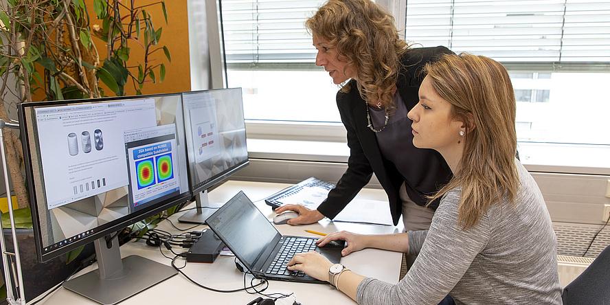 Zwei Frauen an einem Arbeitsplatz mit Laptop und zwei Bildschirmen.