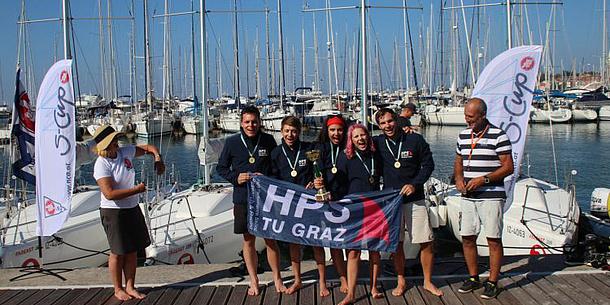 Fünf Studierende halten eine HPS-Flagge, im Hintergrund Segelboote.