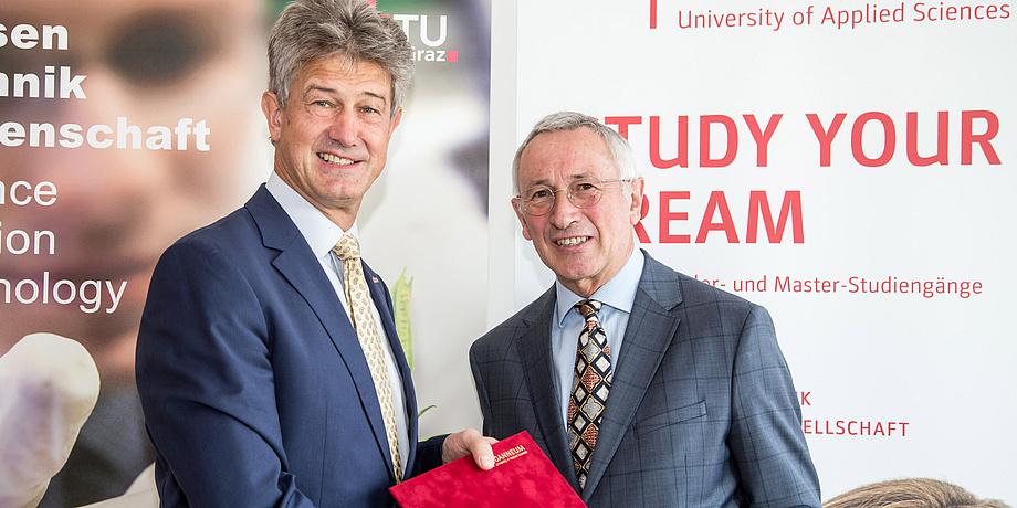 Kainz und Pfeiffer mit dem unterschriebenen Vertrag vor den Rollups der beiden Hochschulen