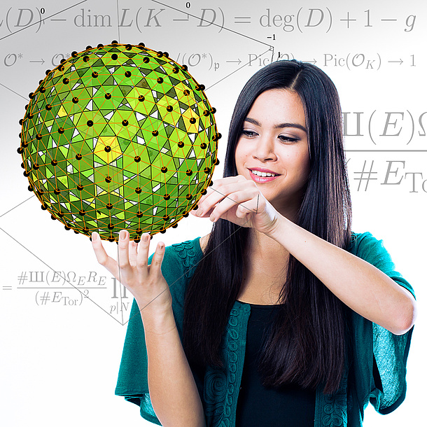 A female student is looking at a polyhedron. In the background you can see mathematical formulas.
