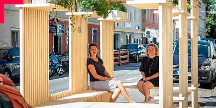Two TU Graz researchers sit in a temporary installation (street furniture) made of wood