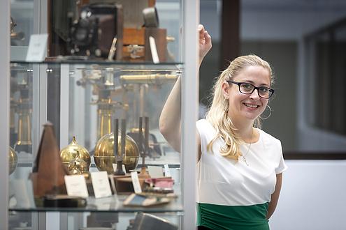 Frau mit Brille neben metallenen Gegenständen