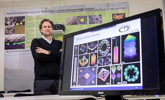 Ein Forscher neben einem Bildschirm mit Abbildung von Nanostrukturen