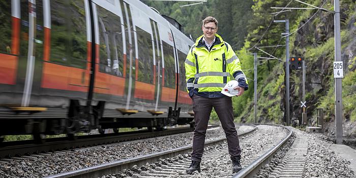 Ein Mann steht auf einem Gleis. Neben ihm fährt ein Zug vorbei.