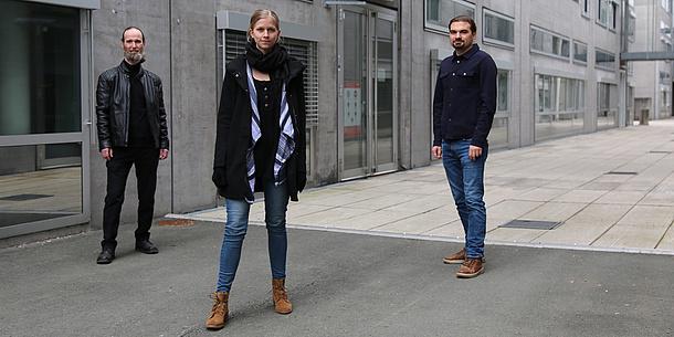 Eine Frau und zwei Männer stehen vor einem grauen Gebäude.