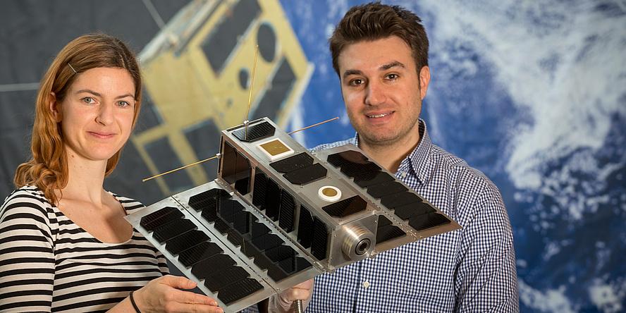 Eine Studentin und ein Student der TU Graz halten den Nanosatelliten OPS-SAT in Händen.