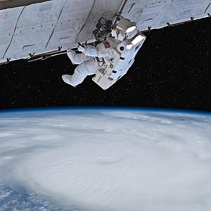 Dieses Bild zeigt einen amerikanischen Astronauten während eines Außeneinsatzes im Weltall. Der Astronaut trägt dabei einen weißen Weltraumanzug, welcher zusätzlich mit einigen Werkzeugen und Überlebenssystemen ausgestattet ist. Der Astronaut ist mi