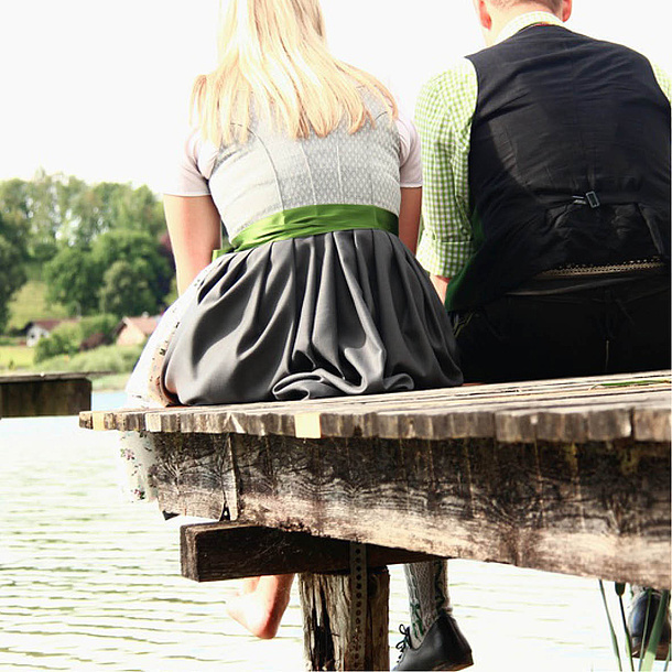 Man and woman in traditional garments sitting on a bridge. Photo source: WoGi - fotolia.com