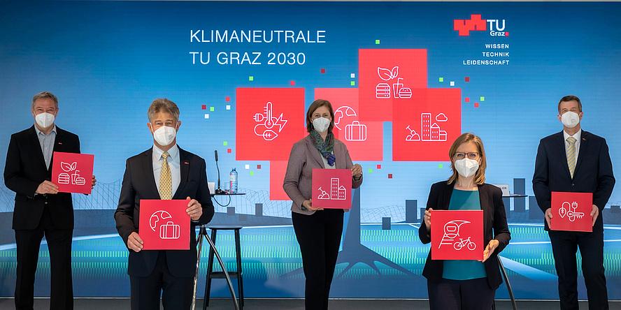 Drei Männer und zwei Frauen mind MNS-Schutz und Tafeln vor einer LED-Leinwand