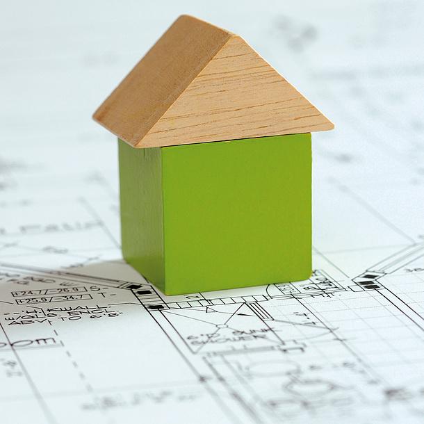 Ein Haus aus Bauklötzen steht auf einem Bauplan. Bildquelle: Stockphoto