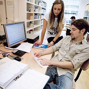 Ein junger Mann und eine junge Frau in einer Bibliothek. Sie blicken auf ein Blatt Papier. Bildquelle: Lunghammer – TU Graz