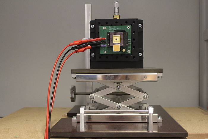 a small silver lifting platform with a black cube on it. A green plate is attached to the cube, on which a black cube is attached. From the green plate come three cables - two red, one black.