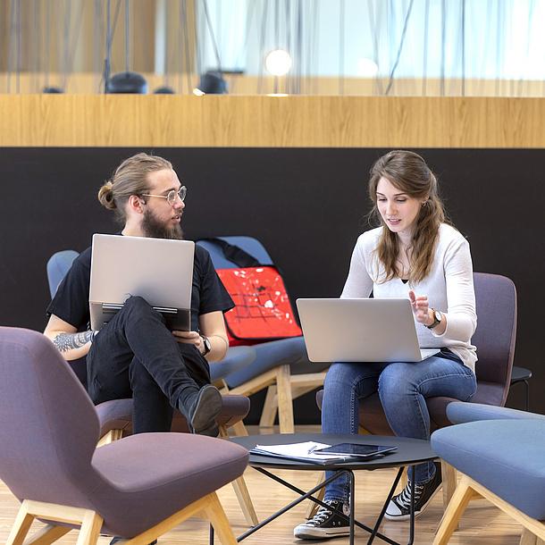 Ein Mann und eine Frau in Loungesesseln mit Laptops am Schoß.