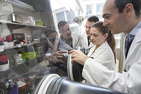 Ilie Hanzu, eine Mitarbeiterin und ein Mitarbeiter vor einer Glovebox.
