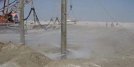 A large pit is enveloped in a cloud of sand; Workers are seen working the soil.