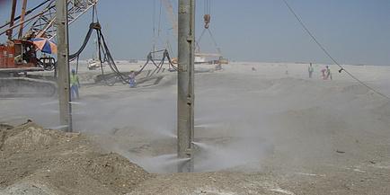 Eine große Baugrube ist eingehüllt in eine Sandwolke; Arbeiter sind zu sehen, die den Baugrund bearbeiten.