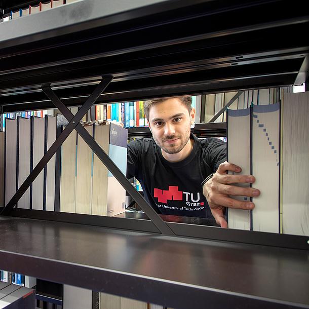 Ein junger Mann in TU Graz T-Shirt blickt durch ein Bücherregal.