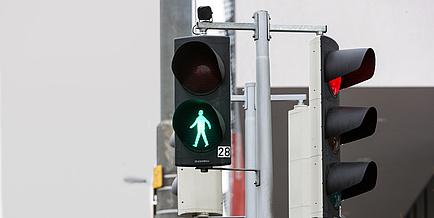 Straßensituation mit Fußgängerampel, die auf grün ist.