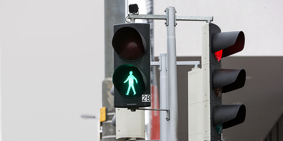 Street situation with pedestrian light on green.