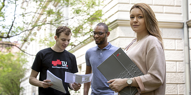 A young woman looks into the camera, holding a TU Graz folder in her hand. In the background two young men look at a piece of paper, one of them is wearing a TU Graz shirt.