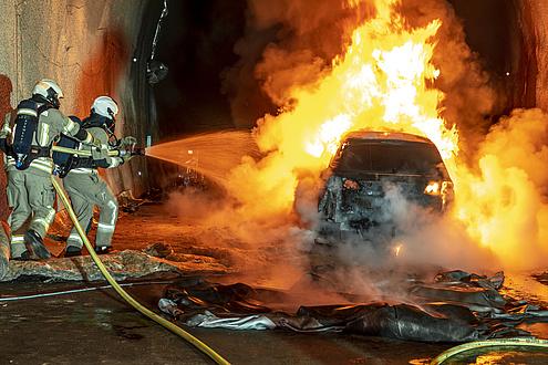 Zwei Feuerwehrleute spritzen Wasser auf ein brennendes Auto.