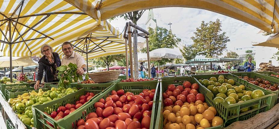 Marktstand mit Tomaten, Paprika und anderen Gemüsesorten groß im Bild, im Hintergrund der Marktplatz.