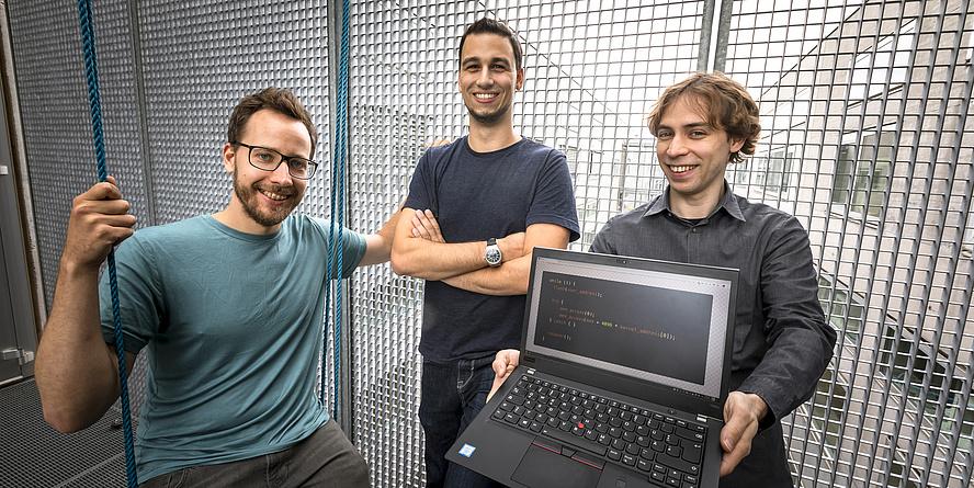 Moritz Lipp, Michael Schwarz und Daniel Gruss stehen in einem Durchgang. Daniel Gruss hält einen Computer, auf dem weißer Text auf schwarzem Hintergrund zu sehen ist.