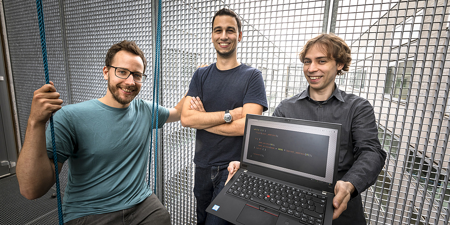 Moritz Lipp, Michael Schwarz and Daniel Gruss. Daniel Gruss holds a laptop computer with white text written on a black screen.