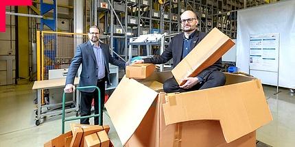 Zwei Männer im Anzug mit Papierschachteln in Logistikzentrum.