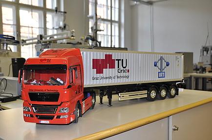 Ein gelber und ein roter Modell LKW fahren in einer Versuchanordnung hintereinander im Testlabor