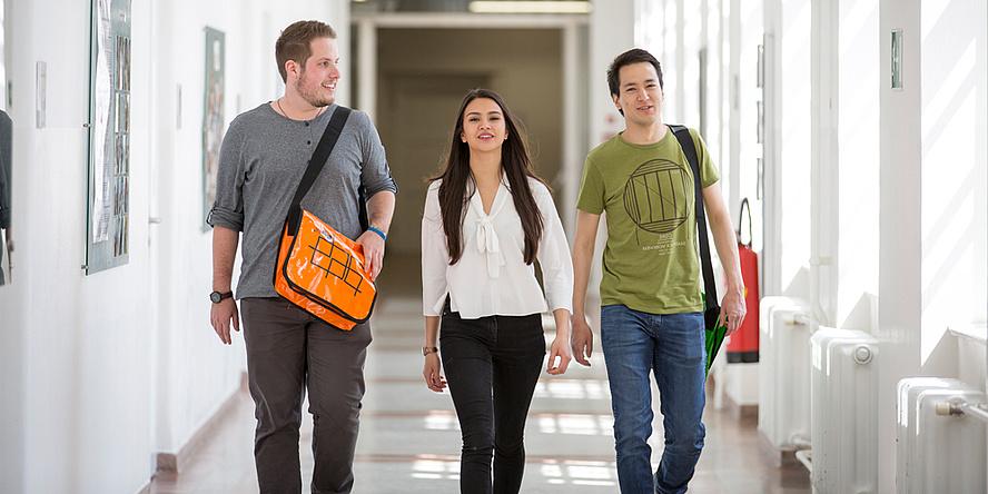 Eine Studentin und zwei Kollegen gehen schwungvoll und gut gelaunt durch einen Gang an der TU Graz.