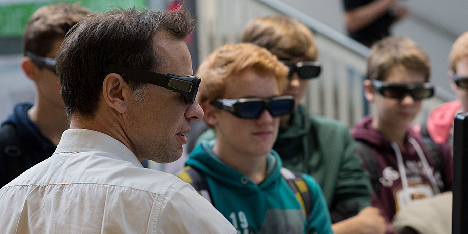 A TU Graz researcher surrounded by pupils at the Geoday. All wear VR goggles while looking at a screen which is hardly to be seen on the edge of the image.