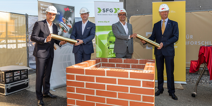 Four men with construction helmets in front of a wall with foundation stone rolls