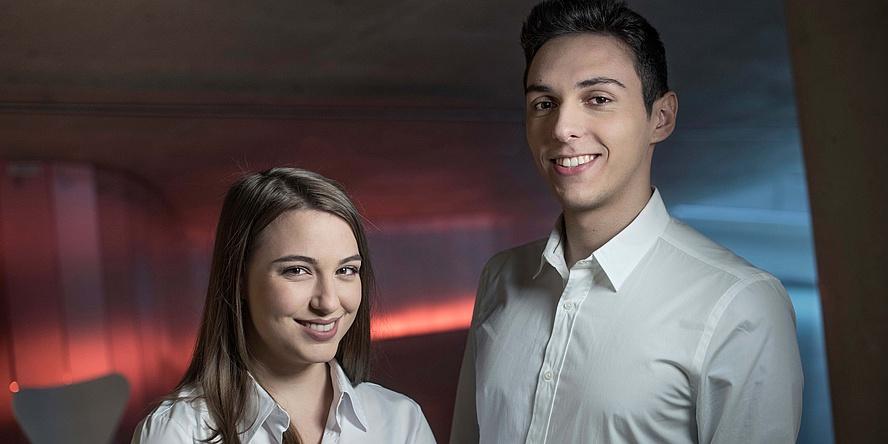 Junge Frau und junger Mann im Porträt vor rot-blaue beleuchtetem Hintergrund