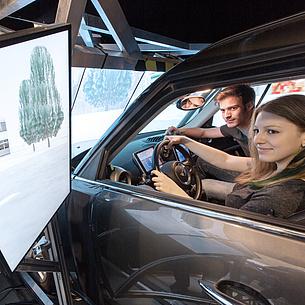 Eine Studentin und ein Student sitzen in einem Fahrsimulator.