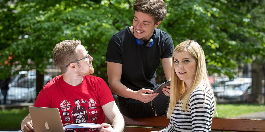 Zwei Burschen und ein Mädchen -  alle Studierende der TU Graz - unterhalten sich im Park miteinander. Vor ihnen ein Laptop.