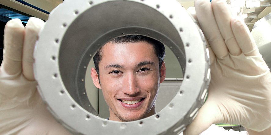 A friendly smiling young man looks through a round metal object into the camera, the TU Graz logo can be seen on the white polo shirt.