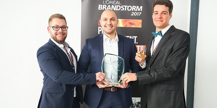 Die drei stolzen Gewinner der L'Oréal Brandstorm Tech-Challenge-Vorausscheidung halten gemeinsam den gläsernen Preis (von links nach rechts): Aleksandar Sargic (mit Bart und Brille), Stefan Stevanovic und Omar Saracevic.