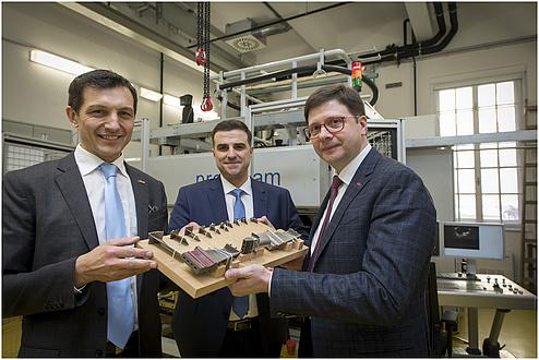 Auf dem Bild sind drei Herren zu sehen, die ein Brett mit Werkstoffproben in die Kamera halten.